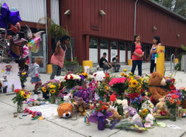 Neighbors look at the growing memorial of flowers, stuffed animals and notes left in memory of Madyson Middleton in Santa Cruz, Calif., Wednesday, July 29, 2015. The close-knit community of artists in Northern California are grieving the death of the 8-year-old girl whose body was found in a trash bin at their housing complex and expressed shock that one of their own, a teenage boy, has been arrested in her death.