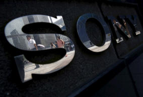 Pedestrians are reflected in a logo of Sony Corp outside its showroom in Tokyo, Japan, June 23, 2015.
