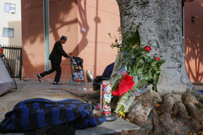 This March 2, 2015 file photo shows a pedestrian walks past flowers and candles placed on a sidewalk near where Charly Keunang a homeless man was shot and killed by police in the Skid Row section of downtown Los Angeles. An officer dropped a nightstick during the struggle with Keunang and the woman who picked it up now faces an assault charge that could send her to prison for 25 years to life. The March shooting was captured on video, which shows Trishawn Cardessa Carey, 34, briefly lifting the baton as police scuffled with Keunang.