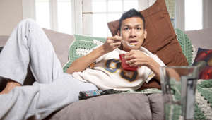 Man eating on couch.