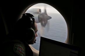 In this March 22, 2014 file photo, flight officer Rayan Gharazeddine on board a Royal Australian Air Force AP-3C Orion, searches for the missing Malaysia Airlines Flight MH370 in southern Indian Ocean, Australia.