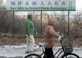 Chinese villagers walks past a notice board on display near the Miyun reservoir, north of Beijing, China.