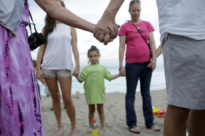 People join hands during a vigil for Austin Stephanos and Perry Cohen, Tuesday, July 28, 2015, in Stuart, Fla. The teenagers have been missing since last Friday when they went out on a boat to go fishing from Tequesta, Fla. A search continues for the boys from the Atlantic waters off Daytona Beach, Florida, north through Savannah, Ga.