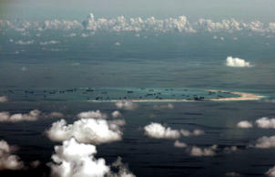 This aerial file photo taken May 11, 2015 through a glass window of a military plane shows China's alleged on-going reclamation of Mischief Reef in the Spratly Islands in the South China Sea.