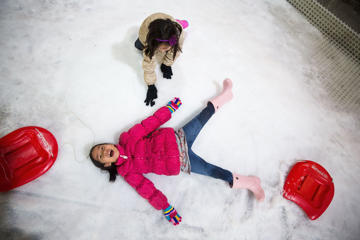 A girl makes a snow angel at Snow Town Bangkok on July 28, 2015 in Bangkok, Thailand.