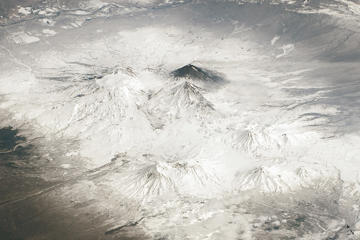 An aerial photograph of the Kamchatka Peninsula in far eastern Russia captured by an astronaut from the International Space Station. The three largest volcanoes in the center of the image include, from left to right, Ushkovsky, Bezymianny and Klyuchevskoy. Tolbachik juts out from the bottom of the image.