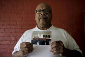 Ronald Cook holds a photograph of himself & grandson Devin Cook in Baltimore, Maryland July 24, 2015.