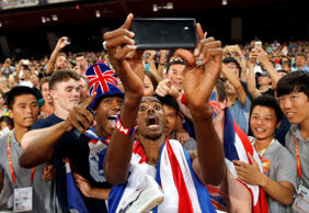 Britain's Mo Farah has a selfie taken with spectators as he celebrates after winning the gold medal in the men's 5000m final at the  World Athletics Championships at the Bird's Nest stadium in Beijing, Saturday, Aug. 29.