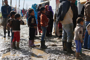 Syrian refugees stand on muddy ground at a refugee camp in Zahle in the Bekaa va...