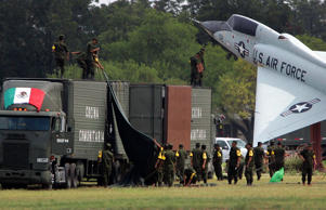 Mexican troops set-up a mobile kitchen in front of a static display of a jet after they arrived Thursday afternoon Sept. 8, 2005, at KellyUSA in San Antonio. The convoy of about 200 unarmed soldiers and medical personnel traveled to aid recovery from Hurricane Katrina. William Luther/San Antonio Express-News/AP