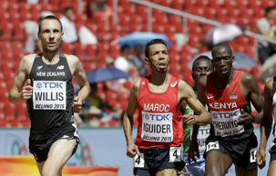 New Zealand's Nick Willis, left, eases up after crossing the line to finish a round one heat of the men's 1500m at the World Athletics Championships at the Bird's Nest stadium in Beijing, Thursday, Aug. 27, 2015.