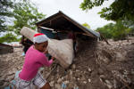 Residents salvage a mattress from a home partially submerged in mud from a mudslide triggered by Tropical Storm Erika, in Montrouis, Haiti, Saturday, Aug. 29, 2015. Erika dissipated early Saturday, but it left devastation in its path on the small eastern Caribbean island of Dominica, and parts of Haiti authorities said.