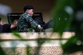 Thai police and army officers escort a suspect in the August 17 Bangkok shrine b...