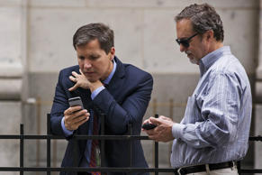Men look at their phones in New York City on August 24, 2015.