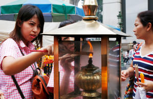 In this Aug. 26, 2015, file photo, worshippers light sticks of incense at the Erawan Shrine at Rajprasong intersection, in Bangkok, Thailand.