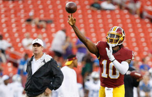 Washington Redskins quarterback Robert Griffin III throws the ball during warm-ups as Redskins head coach Jay Gruden looks on prior to the Redskins game against the Detroit Lions on Aug. 20.