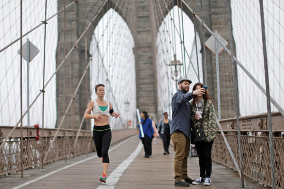 Διαφάνεια 3 από 31: FILE - This May 9, 2015 file photo shows a jogger runing past Jeff Meyer, center, of  West Hempstead, N.Y., and DeAnna Fraietta, of Houston, as they pose for a selfie on the Brooklyn bridge in New York.  New York has opened a number of major new attractions lately, including the Whitney Museum and One World Trade Center observatory, but classics like the Brooklyn Bridge and Times Square are also always at the top of visitors' lists.