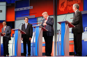 Fellow Republican 2016 U.S. presidential candidates Dr. Ben Carson (L), Wisconsin Governor Scott Walker (2nd L) and former Florida Governor Jeb Bush (R) laugh as fellow candidate and businessman Donald Trump (2nd R) reacts near the end of the debate after realizing that a slew of criticisms spoken by fellow candidate and former Arkansas Governor Mike Huckabee (not pictured) were not aimed at him but at Democratic presidential candidate Hillary Clinton, at the first official Republican presidential candidates debate of the 2016 U.S. presidential campaign in Cleveland, Ohio, August 6, 2015.