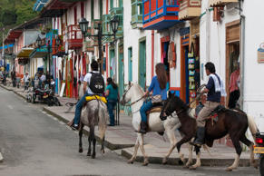 Tourists ride horses through the streets of Salento, Quindio, Colombia.