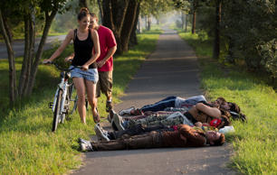 Local cyclists move past a group of Afghan men who crossed from nearby Serbia and sleeping on a bicycle path in Morahalom, Hungary, Sunday, Aug. 30, 2015.
