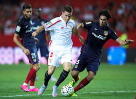 File: Kevin Gameiro (2ndL) of Sevilla FC competes for the ball with Tiago Mendes (R) of Atletico de Madrid and his teammate Yannick Carrasco during the La Liga match between Sevilla FC and Club Atletico de Madrid at Estadio Ramon Sanchez Pizjuan on August 30, 2015 in Seville, Spain.