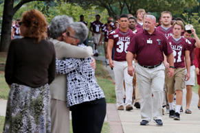 Members of the Salem High school football team arrive to remember alumnus WDBJ-TV cameraman Adam Ward, as mourners hug at Salem High School in Salem, Va., Monday, Aug. 31, 2015.