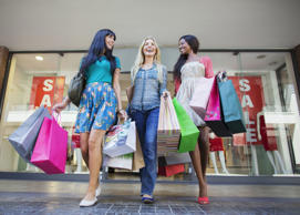 Low angle view of women carrying shopping bags outside clothing store