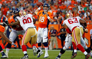 Denver Broncos quarterback Peyton Manning throws as San Francisco 49ers defensive tackle Darnell Dockett, left, and Tony Jerod-Eddie pursue during the first half of an NFL preseason football game, Saturday, Aug. 29, 2015, in Denver.