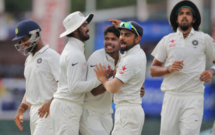 India's Umesh Yadav, center, is congratulated by his teammates for taking the wicket of Sri Lanka's Dimuth Karunarathne, unseen, on the day four of the third test cricket match between them in Colombo, Sri Lanka, Monday, Aug. 31, 2015.