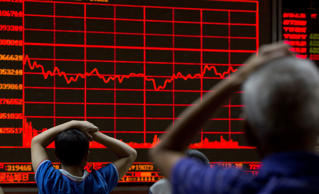 Investors monitor a display showing the Shanghai Composite Index at a brokerage in Beijing, Monday, Aug. 31, 2015.