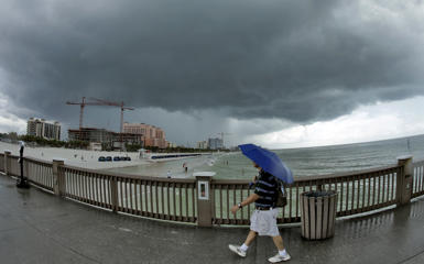 A beach goer leaves the pier on Clearwater beach as a squall from the remains of tropical storm Erika approaches Monday, Aug. 31, 2015, in Clearwater, Fla.