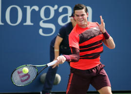 Milos Raonic, of Canada, returns a shot against Tim Smyczek, of the United States, during the first round of the U.S. Open tennis tournament.