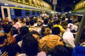 Migrants wait to board a train to Germany at the Keleti Railway Station in Budap...