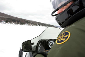 U.S. Border Patrol Agent Andrew Mayer rides a snowmobile as he looks for signs of illegal aliens while crossing a frozen lake that is split between the Canadian territory and the U.S. on March 22, 2006 near Norton, Vt.
