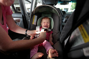 Alexandra Horowitz struggles to strap her daughter, Phoebe, 7 months into her rear-facing car seat at a monthly infant/child carseat inspection held by the Montgomery Fire and Rescue at a Rockville car dealership, Thursday September 15,  2011.