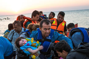 A man carries a girl in his arm as migrants arrive at a coast on a dinghy after crossing from Turkey in the southeastern island of Kos, Greece, during the sunrise early Thursday, Aug. 13, 2015.