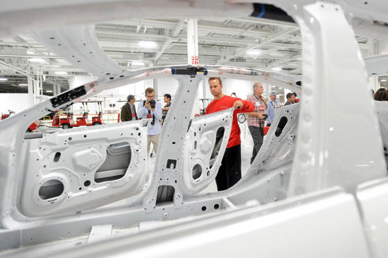 Slide 1 of 11: A Tesla production supervisor, examines a Model S for paint quality at the company's factory in Fremont, California.
