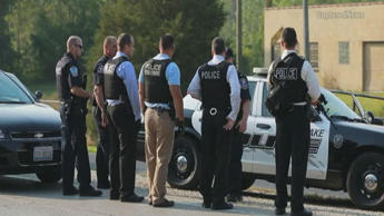 Law enforcement officials at the site where a police officer was fatally shot in...