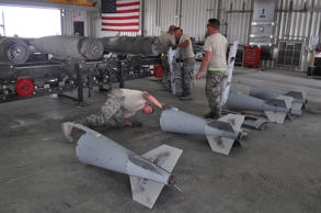 Members of a U.S. Air Force munitions team assemble guided bombs to support the ...
