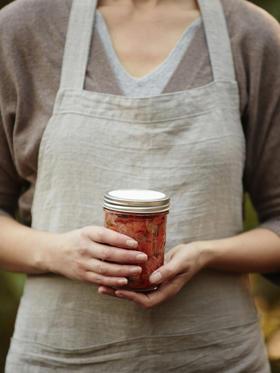 Woman holding jar of fermented sauerkraut vegetables