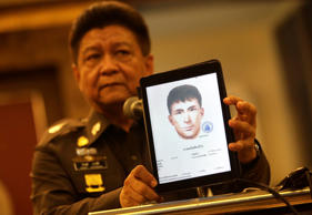 Police spokesman Lt. Gen. Prawuth Thavornsiri shows a photo of one of three men that Thai authorities have issued new arrest warrants in connection with the bombing case, bringing the total number of wanted suspects to seven during a press conference in Bangkok, Thailand, Tuesday, Sept. 1, 2015.