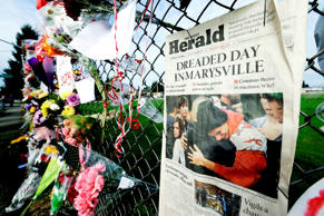 "In this photo taken Oct. 27, 2014, an edition of The Daily Herald from Everett, Wash. with the headline ""Dreaded Day in Marysville"" is shown as part of a growing memorial on a fence around Marysville Pilchuck High School in Marysville, Wash. On Wednesday, Nov. 12, 2014, authorities released the 911 calls from students, parents, neighbors, school workers and teacher Megan Silberberger, who tried to intervene when a freshman student, Jaylen Fryberg, opened fire at a group of friends at the school on Oct. 24, 2014."
