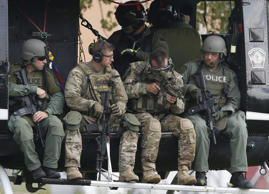 Police officers prepare to take off in a helicopter for a manhunt in Fox Lake, I...