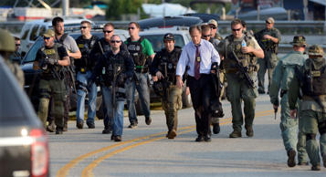 Members of local, state and federal police agencies gather as they continue searching for suspects in the shooting of a police officer Tuesday, Sept. 1, 2015 in Fox Lake, Ill. Fox Lake Police Lt. Charles Joseph Gliniewicz was shot and killed while pursuing a group of suspicious men. Police with helicopters, dogs and armed with rifles are conducting a massive manhunt in northern Illinois for the individuals believed to be involved in the death of the three-decade member of the department and a father of four sons.