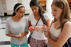 In this July 27, 2015, photo, Isabella Cimato, 17, left, Arianna Schaden, 14, center, and Sofia Harrison, 15, check their phones at Roosevelt Field shopping mall in Garden City, N.Y. Teens aren't roaming around at the mall for kicks during back-to-school. They're researching the looks they want online and follow popular hashtags on social media so they can piece together looks before they get there. Seth Wenig/AP