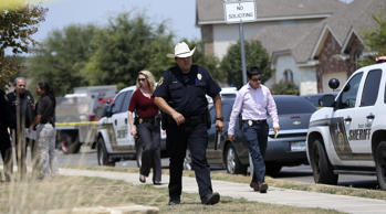 In this photo taken Friday, Aug. 28, 2015, the Bexar County Sheriff's Department investigates the scene where deputies shot a man as they responded to a domestic disturbance call in Northwest Bexar County, Texas, near San Antonio.