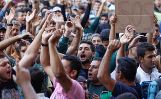 Migrants shout slogans in front of the Keleti Railway Station in Budapest, Hungary, Wednesday, Sept. 2, 2015, as hundreds demanded to be let on trains to Germany. Over 150,000 migrants have reached Hungary this year, most coming through the southern border with Serbia. Many apply for asylum but quickly try to leave for richer EU countries.