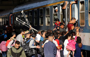 Migrants try to board a train at the railway station in Budapest, Hungary, Thursday, Sept. 3, 2015.