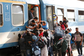 Migrants struggle to board a train at the railway station in Budapest, Hungary, ...