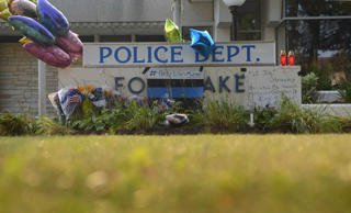 Flowers are placed at a memorial outside of the Fox Lake Police Department as th...